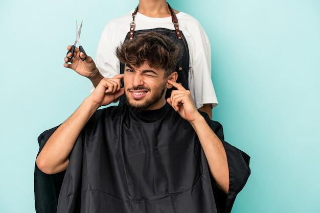 Jeune homme arabe prêt à se faire couper les cheveux isolé sur fond bleu couvrant les oreilles avec les mains.
