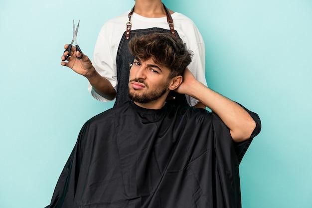 Jeune homme arabe prêt à se faire couper les cheveux isolé sur fond bleu étant choqué, elle s'est souvenue d'une réunion importante.