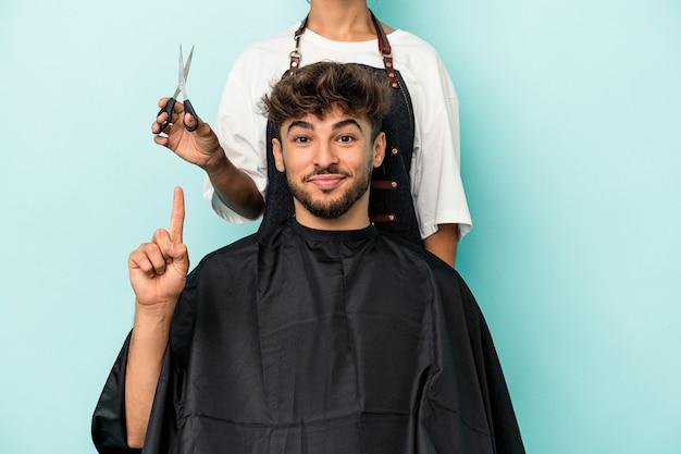 Jeune homme arabe prêt à se faire couper les cheveux isolé sur fond bleu montrant le numéro un avec le doigt.