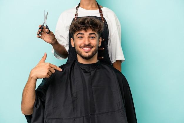 Jeune homme arabe prêt à se faire couper les cheveux isolé sur fond bleu personne pointant à la main vers un espace de copie de chemise, fier et confiant