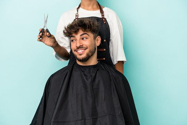 Jeune homme arabe prêt à se faire couper les cheveux isolé sur fond bleu regarde de côté souriant, joyeux et agréable.