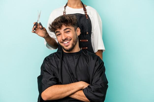 Jeune homme arabe prêt à se faire couper les cheveux isolé sur fond bleu en riant et en s'amusant.