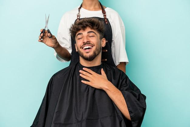 Jeune homme arabe prêt à se faire couper les cheveux isolé sur fond bleu rit fort en gardant la main sur la poitrine.