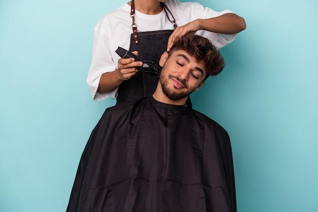 Jeune homme arabe prêt à se faire couper les cheveux isolé sur fond bleu