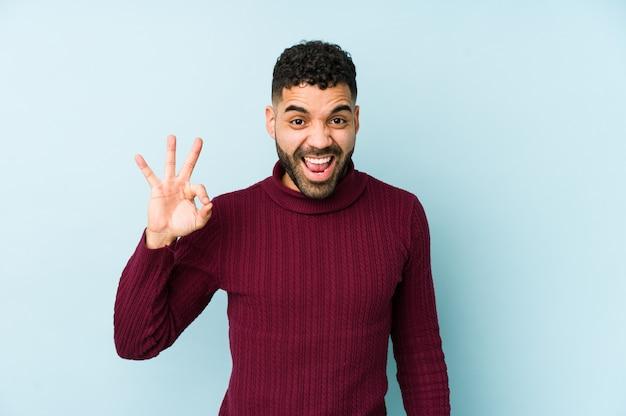 Jeune homme arabe de race mixte isolé fait un clin d'œil et détient un geste correct avec la main.