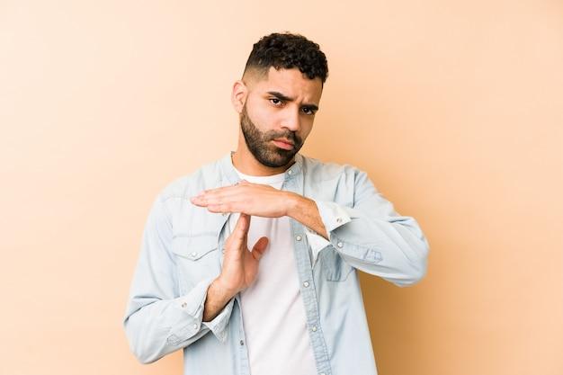 Jeune homme arabe de race mixte isolé montrant un geste de temporisation.