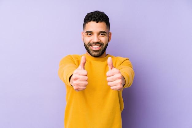 Jeune homme arabe de race mixte isolé avec les pouces vers le haut, acclamations à propos de quelque chose, soutien et respect du concept.