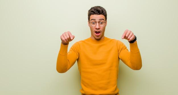 Jeune homme arabe se sentant choqué, bouche bée et étonné, regardant et pointant vers le bas avec incrédulité et surprise contre un mur plat