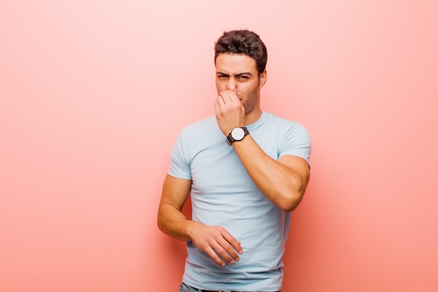 Jeune homme arabe se sentant dégoûté, tenant le nez pour éviter de sentir une odeur nauséabonde et désagréable contre le mur rose