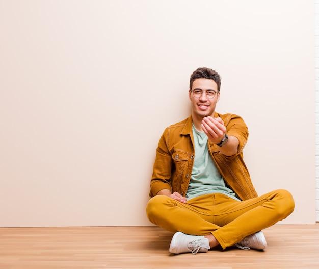 Jeune homme arabe se sentant heureux, réussi et confiant, face à un défi et disant: lancez-le! ou vous accueillir assis par terre