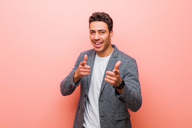 Jeune homme arabe souriant avec une attitude positive, réussie et heureuse pointant, faisant signe de pistolet avec les mains contre le mur rose