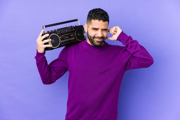 Jeune homme arabe tenant une cassette radio isolée jeune homme arabe écoutant de la musique couvrant les oreilles avec les mains.