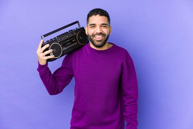 Jeune homme arabe tenant une cassette radio isolée jeune homme arabe écoutant de la musique en riant et en s'amusant.