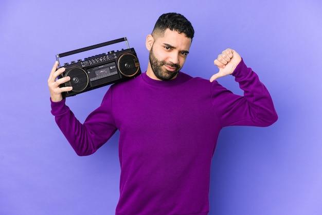 Jeune homme arabe tenant une cassette radio isolée jeune homme arabe écoutant de la musique se sent fier et confiant, exemple à suivre.