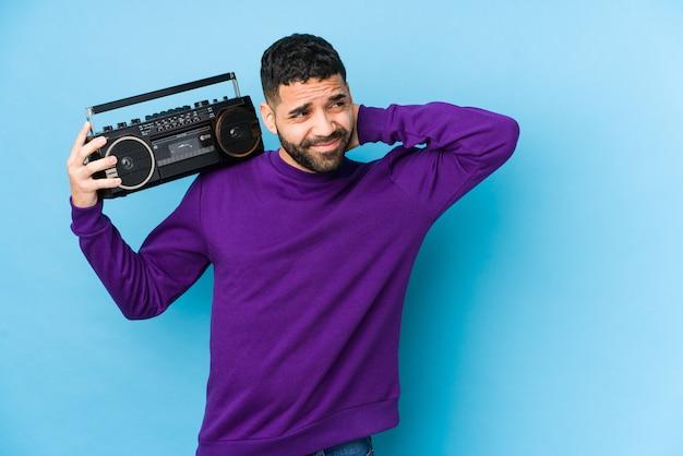 Jeune homme arabe tenant une cassette radio isolée