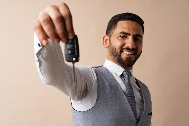 Jeune homme arabe tenant une clé de voiture et la montrant sur fond beige