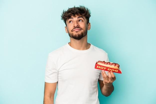 Jeune homme arabe tenant un hot-dog isolé sur fond bleu rêvant d'atteindre des objectifs