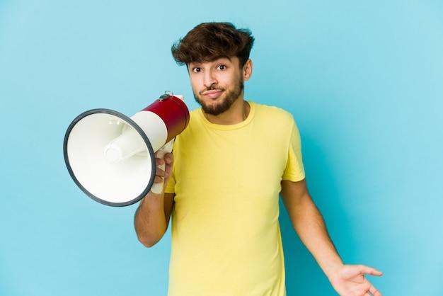 Jeune homme arabe tenant un mégaphone confus, se sent douteux et incertain.