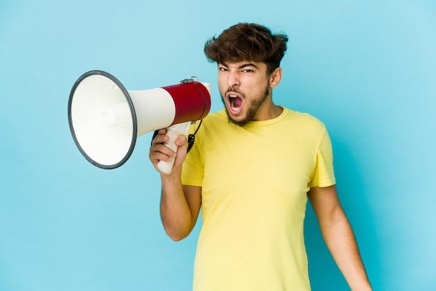 Jeune homme arabe tenant un mégaphone criant très en colère et agressif.