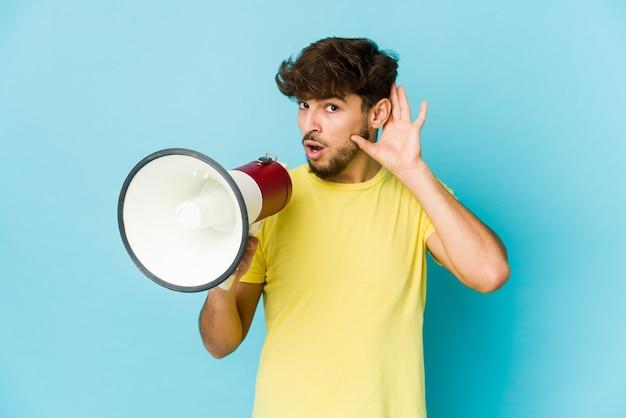 Jeune homme arabe tenant un mégaphone essayant d'écouter un potin.
