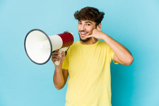 Jeune homme arabe tenant un mégaphone montrant un geste d'appel de téléphone mobile avec les doigts.