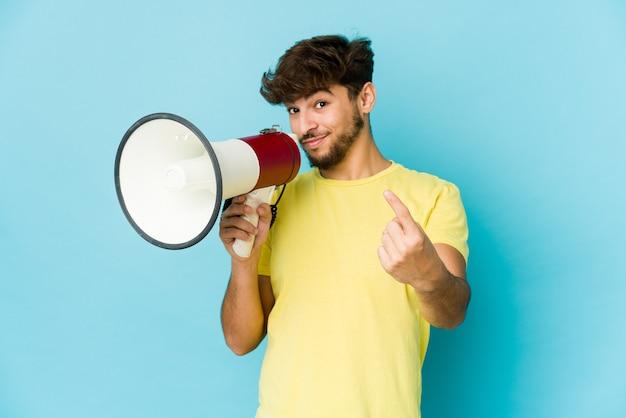 Jeune homme arabe tenant un mégaphone pointant avec le doigt sur vous comme pour vous inviter à vous rapprocher.