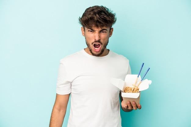 Jeune homme arabe tenant des nouilles à emporter isolées sur fond bleu criant très en colère et agressif.
