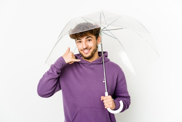 Jeune homme arabe tenant un parapluie montrant un geste d'appel de téléphone mobile avec les doigts.