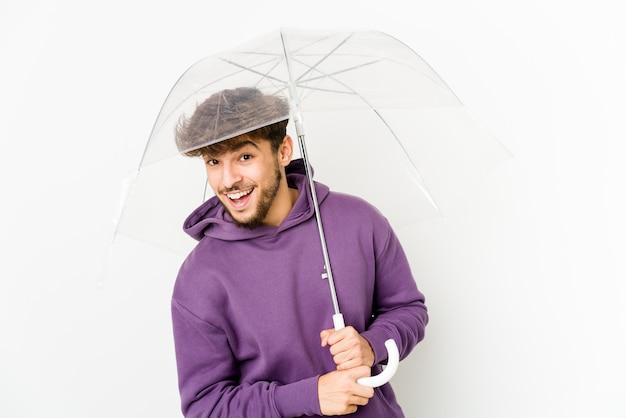 Jeune homme arabe tenant un parapluie en riant et en s'amusant.
