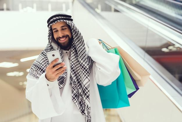 Jeune homme arabe utilisant un téléphone portable dans un centre commercial moderne