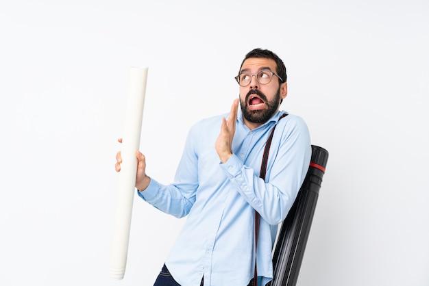 Jeune homme architecte avec barbe sur blanc isolé nerveux et effrayé