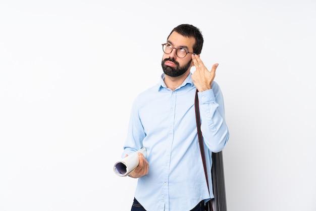 Jeune homme architecte avec barbe sur blanc isolé avec des problèmes de geste de suicide
