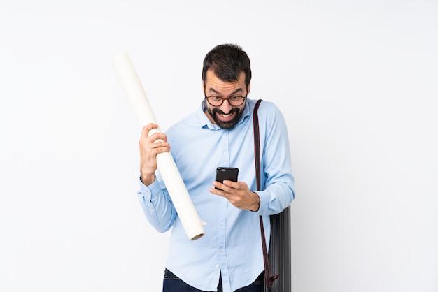 Jeune homme architecte avec barbe sur blanc isolé surpris et en envoyant un message