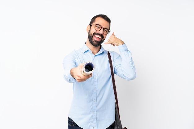 Jeune homme architecte avec barbe faisant geste de téléphone et pointant vers l'avant