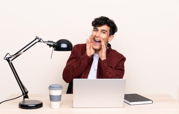 Jeune homme argentin assis à une table avec un ordinateur portable sur son lieu de travail en criant avec la bouche grande ouverte