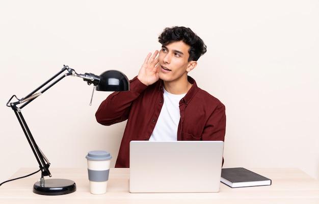 Jeune homme argentin assis à une table avec un ordinateur portable sur son lieu de travail écoutant quelque chose