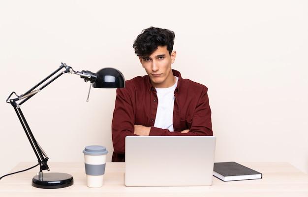 Jeune homme argentin dans une table avec un ordinateur portable dans son lieu de travail triste