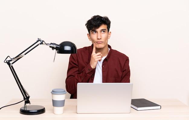 Jeune homme argentin dans une table avec un ordinateur portable sur son lieu de travail en pensant à une idée