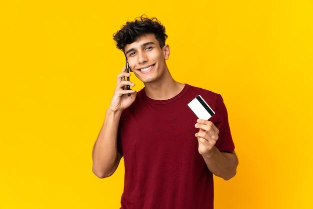 Jeune homme argentin isolé sur mur jaune en gardant une conversation avec le téléphone mobile et tenant une carte de crédit