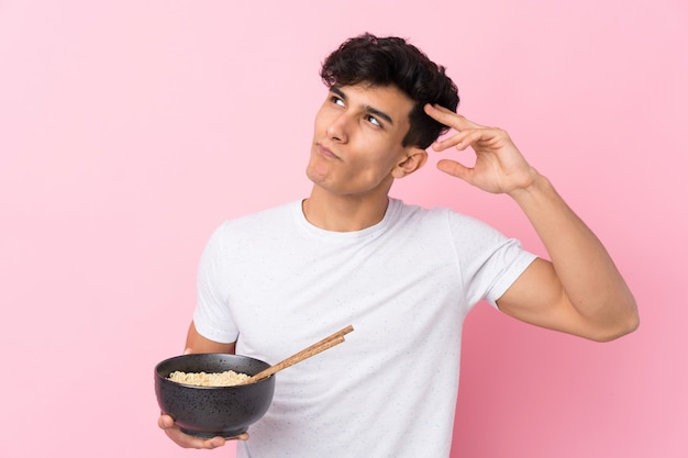 Jeune homme argentin sur mur blanc isolé ayant des doutes et avec une expression du visage confuse tout en tenant un bol de nouilles avec des baguettes