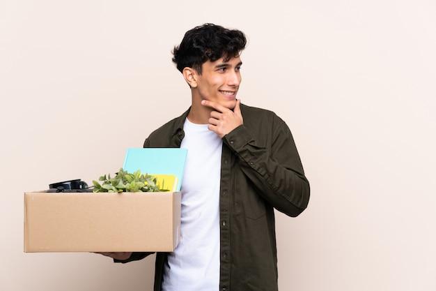 Jeune homme argentin se déplaçant dans une nouvelle maison sur un mur isolé en pensant à une idée et à côté