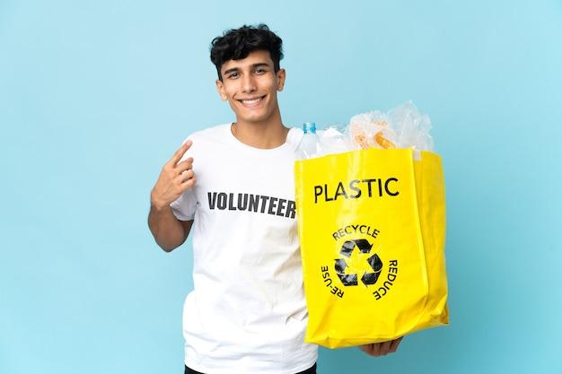 Jeune homme argentin tenant un sac plein de plastique donnant un coup de pouce geste