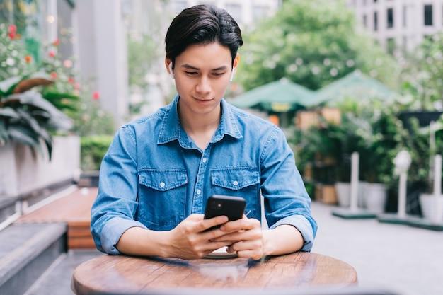 Jeune homme asiatique à l'aide de smartphone au café