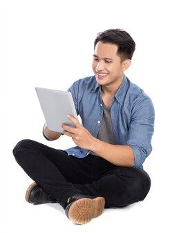 Jeune homme asiatique à l'aide de tablet pc tout en étant assis sur le sol