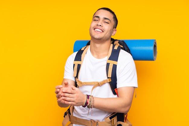 Jeune homme asiatique alpiniste avec un gros sac à dos isolé sur fond jaune applaudissant