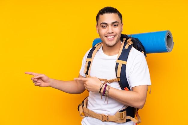 Jeune homme asiatique alpiniste avec un gros sac à dos isolé sur fond jaune doigt pointé sur le côté