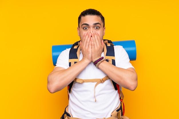 Jeune homme asiatique alpiniste avec un gros sac à dos isolé sur fond jaune avec une expression faciale surprise