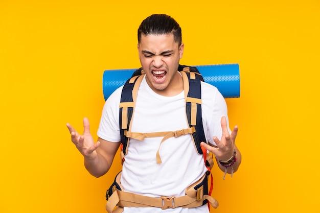 Jeune homme asiatique alpiniste avec un gros sac à dos isolé sur fond jaune malheureux et frustré par quelque chose