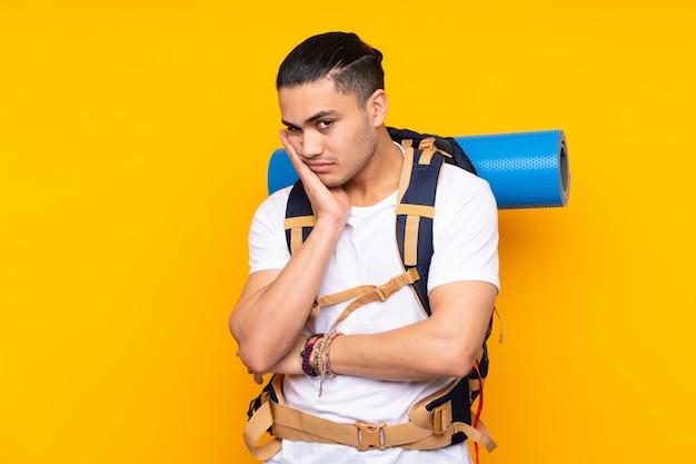 Jeune homme asiatique alpiniste avec un gros sac à dos isolé sur fond jaune malheureux et frustré