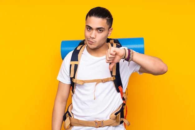Jeune homme asiatique alpiniste avec un gros sac à dos isolé sur fond jaune montrant le pouce vers le bas signe